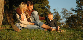 Family sitting on a grassy hill