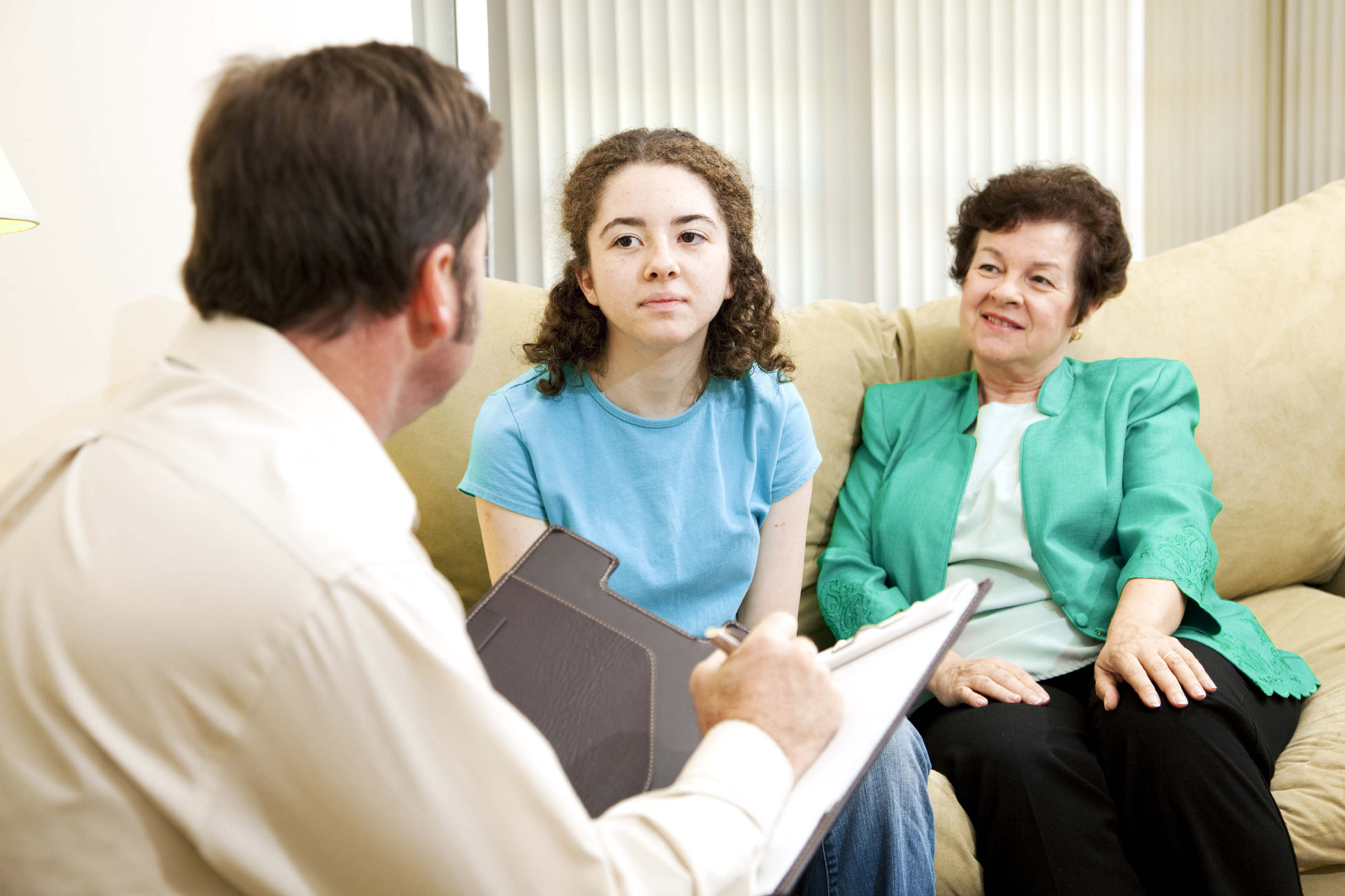 Teenage girl and her mother meeting with a clinician.